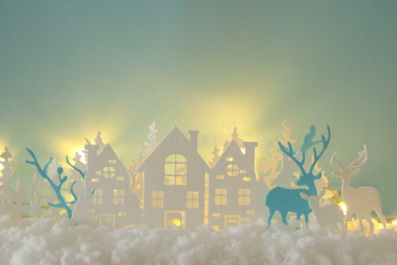 Det magiska landskapet för bakgrund för vintern för julpapperssnittet med hus, träd, hjortar och den insnöade framdelen av guld t arkivfoton