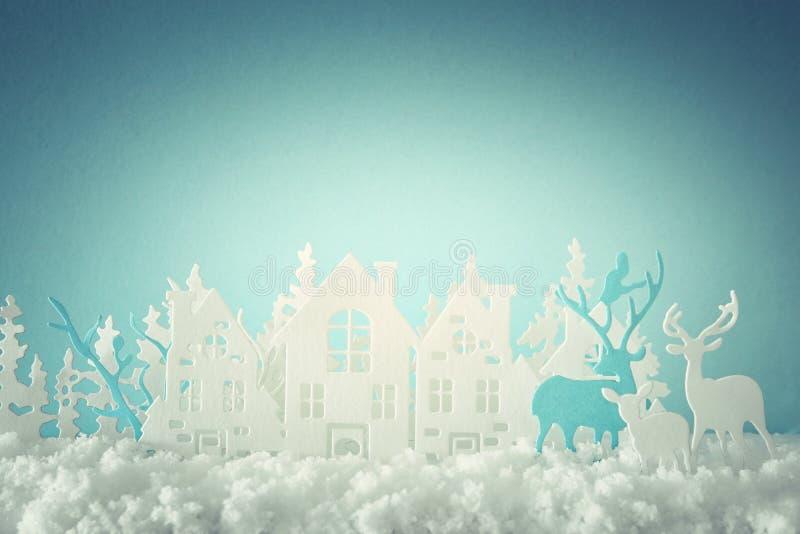 Det magiska landskapet för bakgrund för vintern för julpapperssnittet med hus, träd, hjortar och den insnöade framdelen av pastel royaltyfri illustrationer