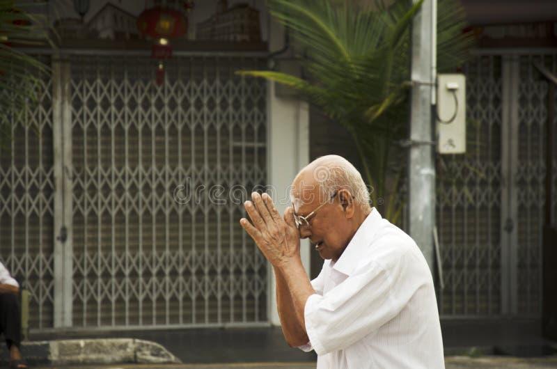 Det malaysiska gamal manfolket ber och betalar respekt till guden royaltyfria foton
