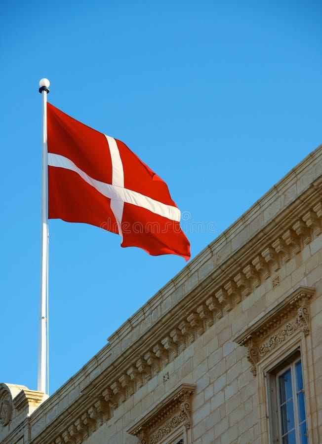 Det maltesiska flaggaslutet upp på taket av byggnad, den malta flaggan i bakgrund för blå himmel, fragmentet, flagga på blåsig dag fotografering för bildbyråer