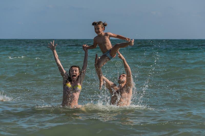 Det mamma-, farsa- och dotterbadet, spelar och har gyckel på havet i semesterorten - en lycklig familj royaltyfria bilder