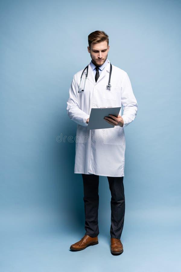 Det manliga doktorsanseendet med mappen, Doc bär den vita likformign, och ett band, står på ett ljust - blå bakgrund fotografering för bildbyråer