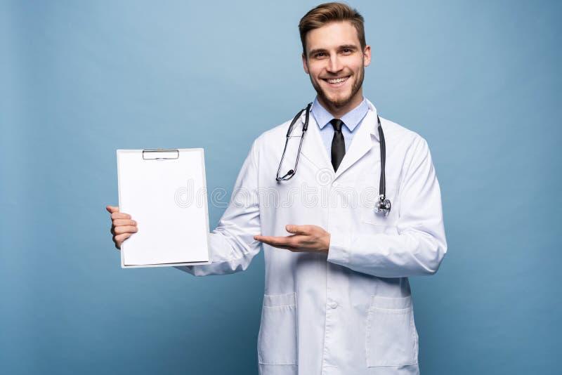 Det manliga doktorsanseendet med mappen, Doc b?r den vita likformign, och ett band, st?r p? ett ljust - bl? bakgrund fotografering för bildbyråer
