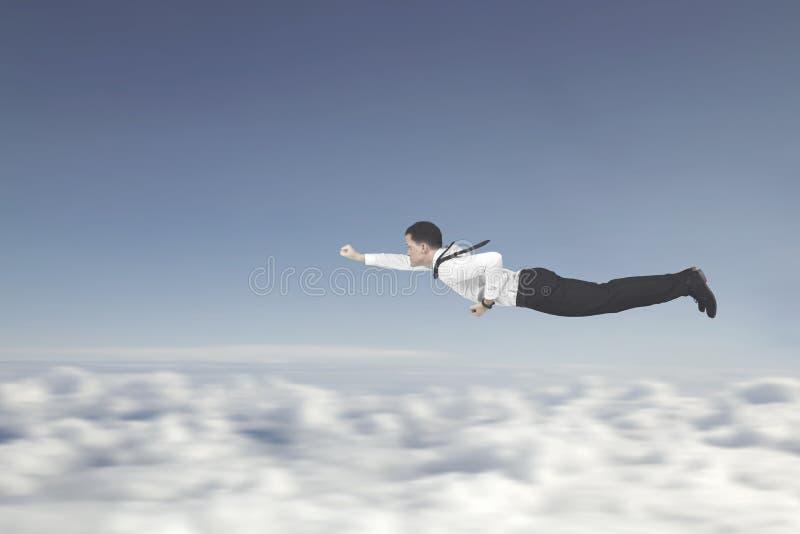 Det manliga entreprenörflyget med en superhero poserar royaltyfria bilder