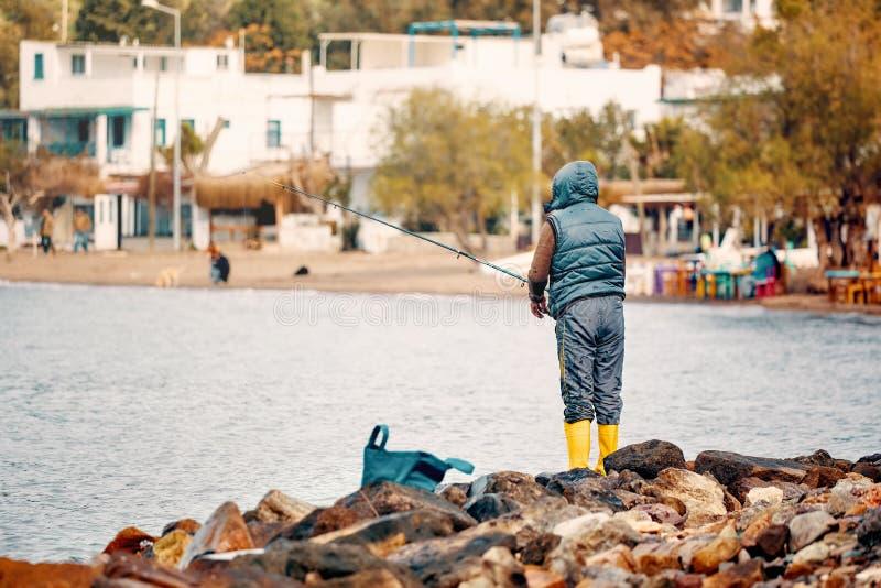 Det manliga fiskareanseendet på vaggar nära sjösidan och att fiska på en molnig vinterdag arkivfoton