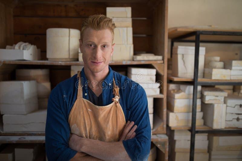Det manliga keramikeranseendet med armar korsade i krukmakeriseminarium royaltyfria foton