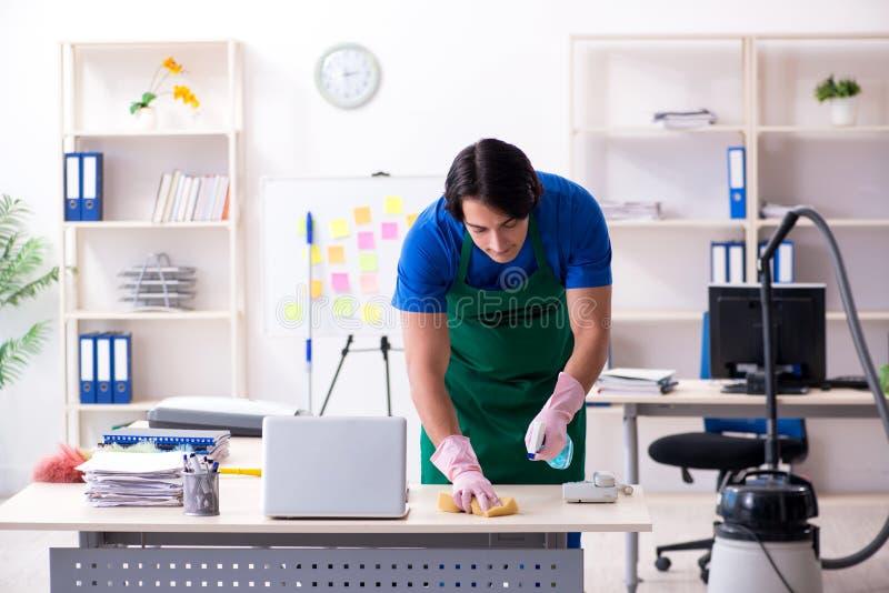 Det manliga stiliga yrkesm?ssiga reng?ringsmedlet som arbetar i kontoret fotografering för bildbyråer