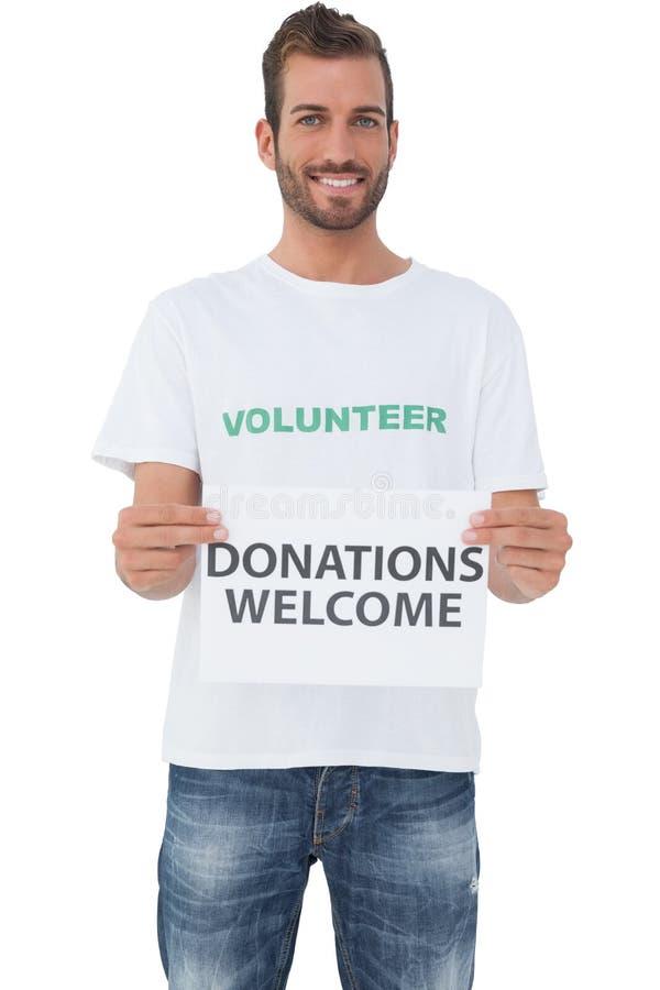Det manliga volontärinnehavet 'donationer välkomnar' papper royaltyfri foto
