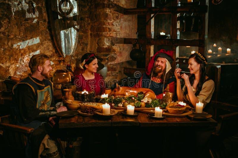 Det medeltida folket äter och dricker i slottkrog arkivbild