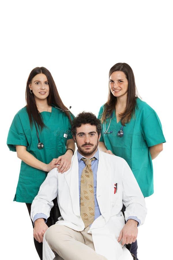 Det medicinska laget med den skäggiga doktorn och härliga kvinnliga kirurger ler Doktorspersonal caucasian Isolerat på vit royaltyfria bilder