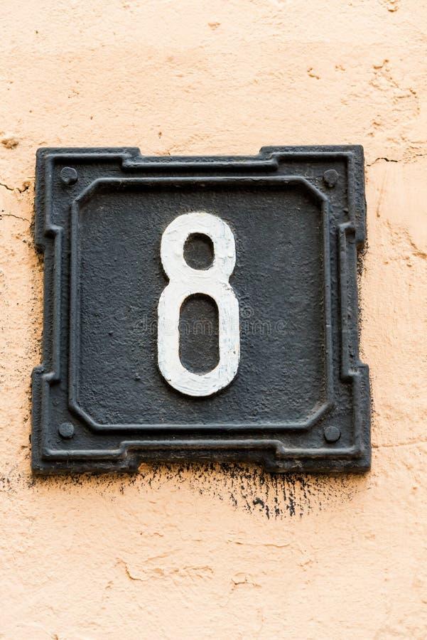 Det metalliska husnumret, svärtar på väggen royaltyfri fotografi