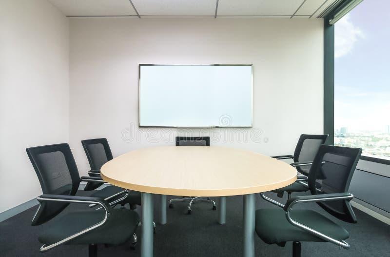 Det metting rummet har det wood skrivbordet och svärtar stolar Kontorsmeettin royaltyfri foto