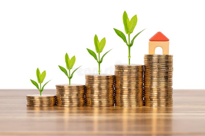 Det mini- modellhuset på myntbuntbegreppet för intecknar, finans och besparingen arkivfoto
