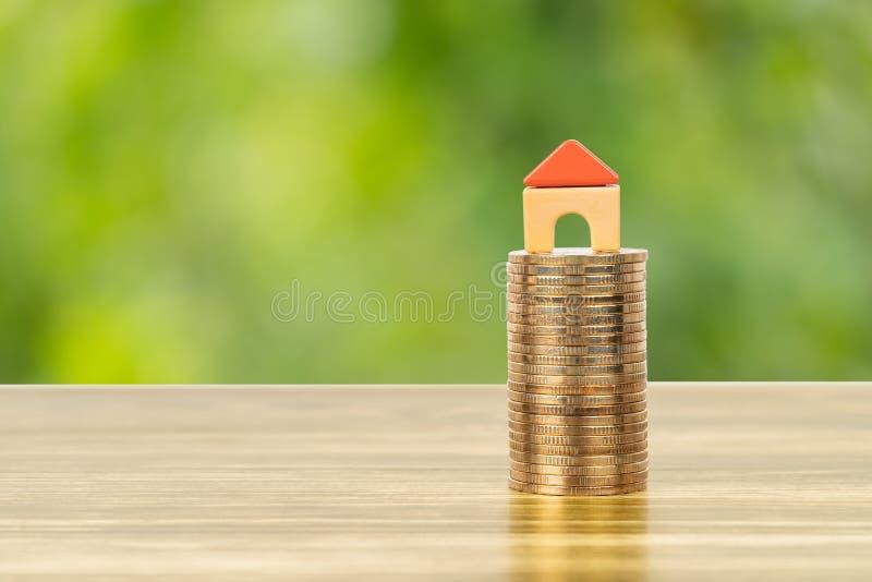 Det mini- modellhuset på myntbuntbegreppet för intecknar, finans och besparingen arkivbilder