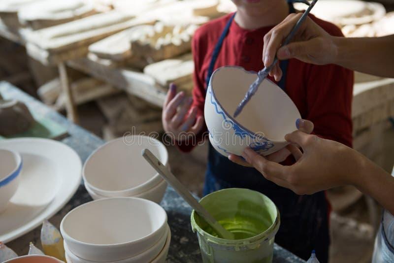 Det mitt- avsnittet av kvinnlig keramiker- och pojkemålning bowlar arkivfoton