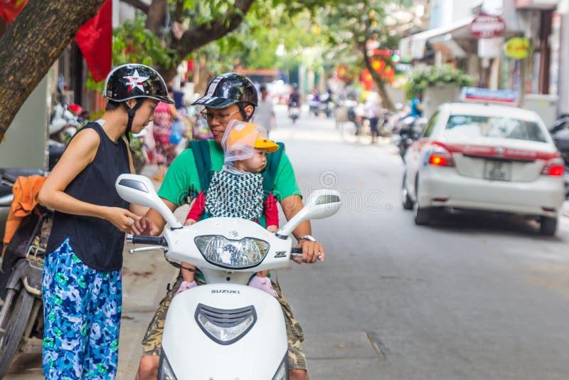 Det moderfadern och barnet behandla som ett barn in bäraren på sparkcykeln i Hanoi, VI royaltyfri fotografi