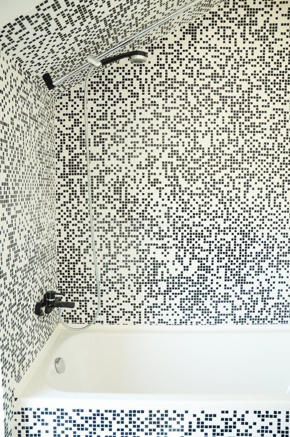 Det moderna badet badar med duschen, kromvattenkranen och moderna mosaiktegelplattor royaltyfria foton