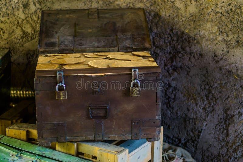 Det moderna begreppet av a piratkopierar skattbröstkorgen som fylls med guld- bitcoins, cryptocurrencybegrepp arkivbilder