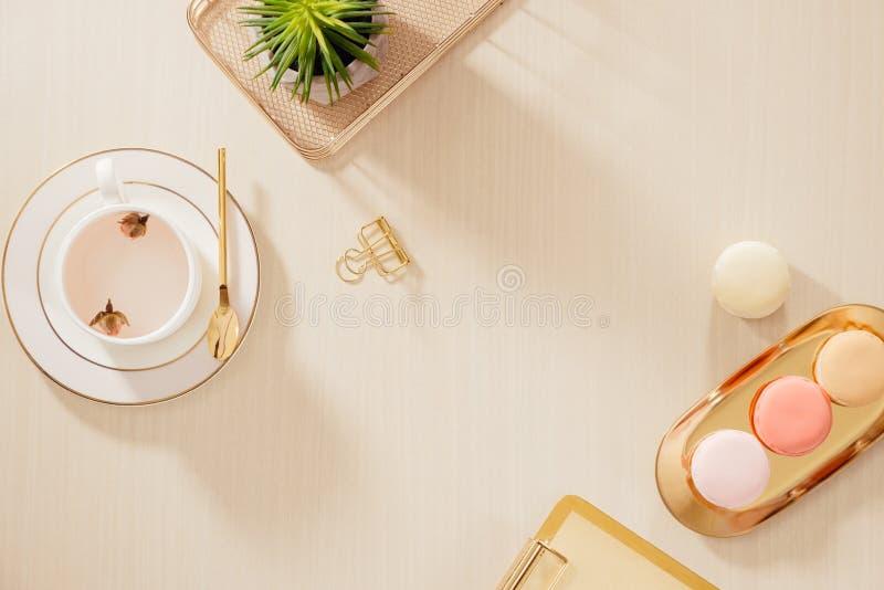 Det moderna guld- stiliserade inrikesdepartementetskrivbordet med mappen, makron, kaffe rånar på beige bakgrund L?genheten l?gger royaltyfria bilder