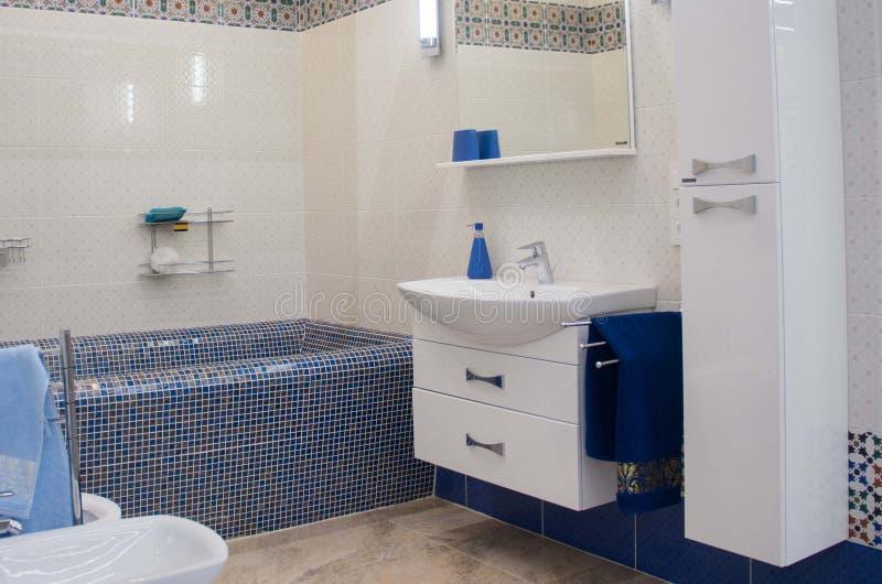 Det moderna lyxiga badrummet med det stora badet badar och mosaiktegelplattor royaltyfri bild