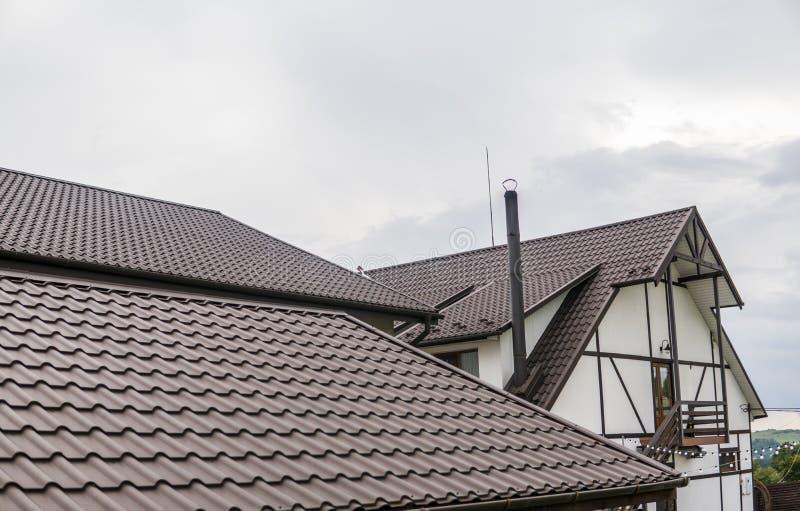 Det moderna taket som täckas med taket för metall för tegelplattaeffekt det PVC täckte bruna, täcker royaltyfria bilder