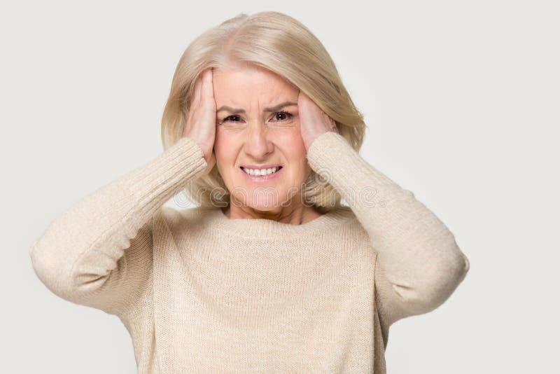 Det mogna kvinnainnehavhuvudet i händer känner det sjukliga studioskottet royaltyfri bild