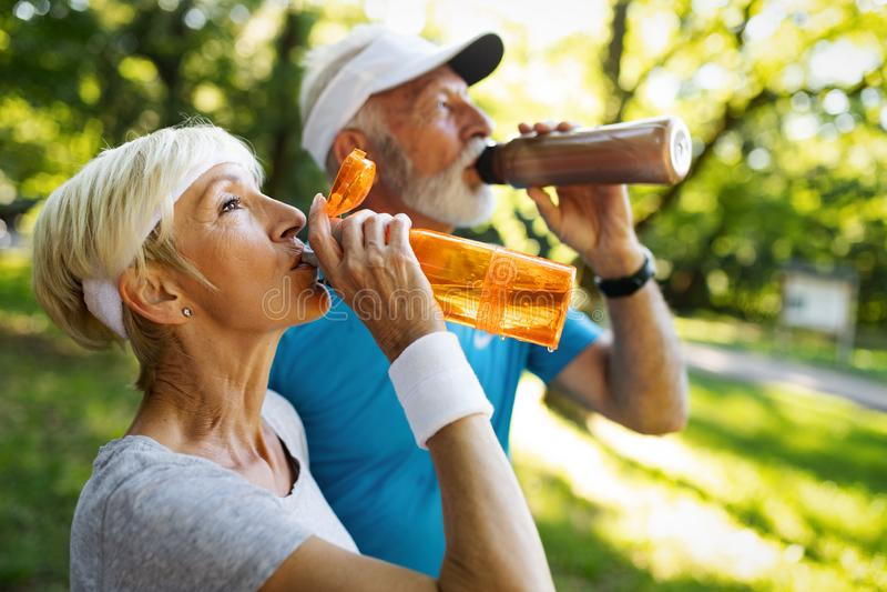 Det mogna paret dricker vatten för att fylla på energi och för att hydratisera arkivfoto