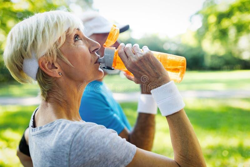 Det mogna paret dricker vatten f?r att fylla p? energi och f?r att hydratisera royaltyfri bild