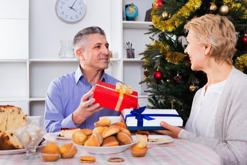 Det mogna paret ger gåvor till varandra för jul för festiv royaltyfri foto