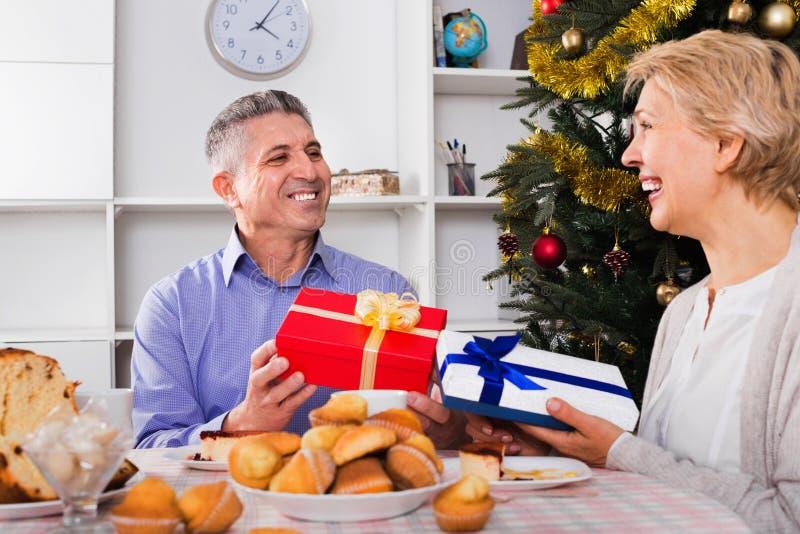 Det mogna paret ger gåvor till varandra för jul för festiv royaltyfri bild