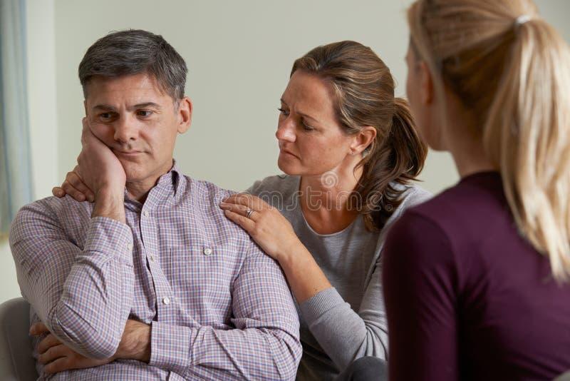 Det mogna paret som talar med rådgivaren som kvinna, tröstar mannen royaltyfri foto