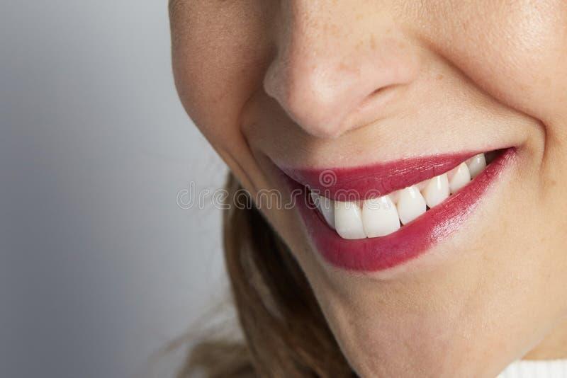 Det monokromma skottet av den lyckliga caucasian affärskvinnan med positivt leende, har knaprigt mörkt hår, på den vita väggen arkivfoton