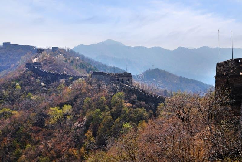 Det Mutianyu avsnittet av den stora väggen av Kina i en solig vårdag, mot en blå himmel royaltyfri bild