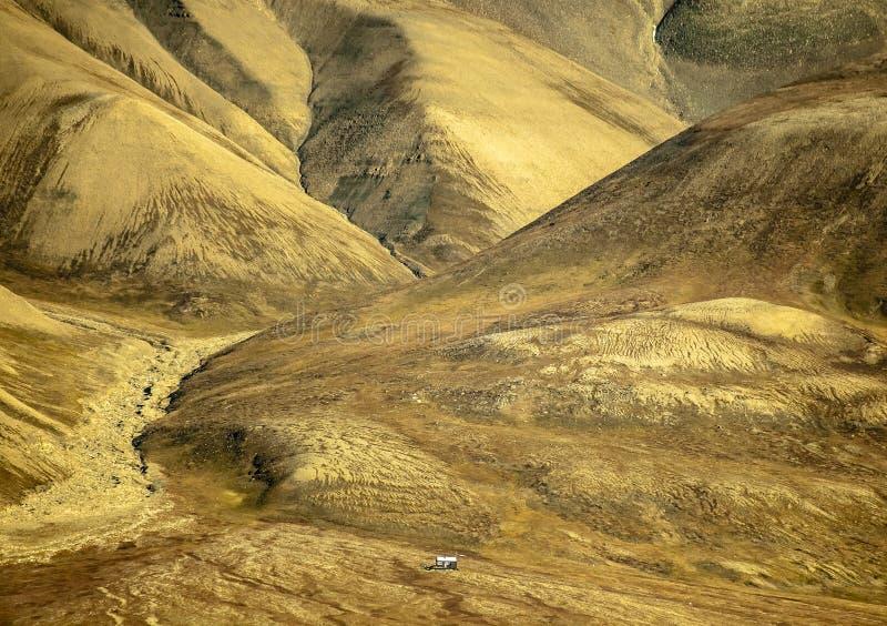 Det mycket lilla ensamma huset för forskare står på foten av berget arkivbild