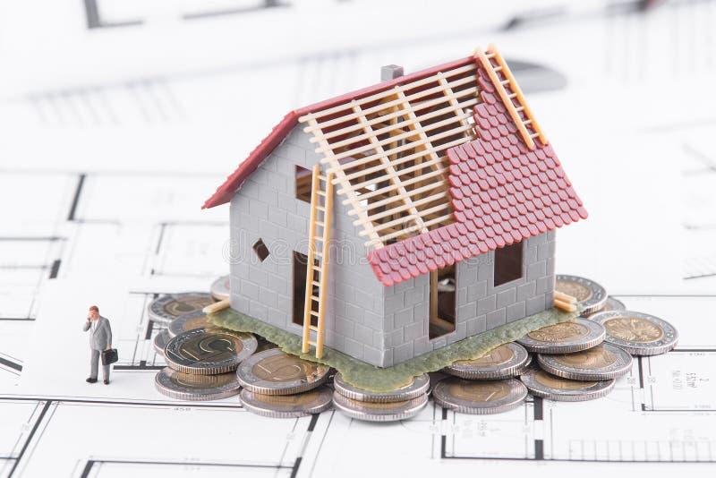 Det mycket lilla huset står på mynt Begreppet av bankrörelsen, lån, expen arkivbild
