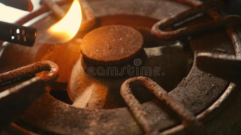 Det nära övre detaljskottet av den gamla rostiga cirkeln för kökugnen kopplade på brand med ljusare flammabränning i farlig gasen arkivfoton