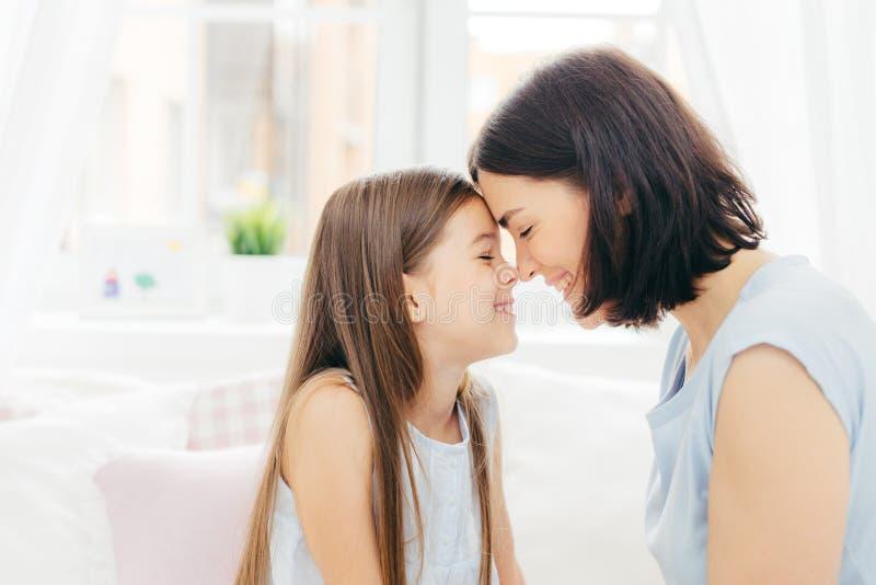 Det nära övre skottet av den tillgivna unga modern och hennes lilla dotterhandlagnäsor och att tycka om samhörighetskänsla, poser arkivfoton