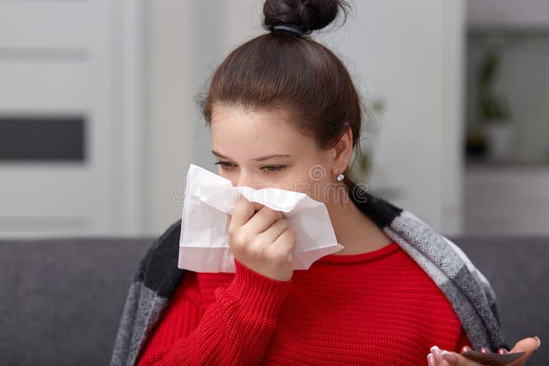 Det nära övre skottet av kvinnan nyser och har dåligt den rinnande näsan som slås in i sängöverkast, rymmer mobiltelefonen, och s arkivbild