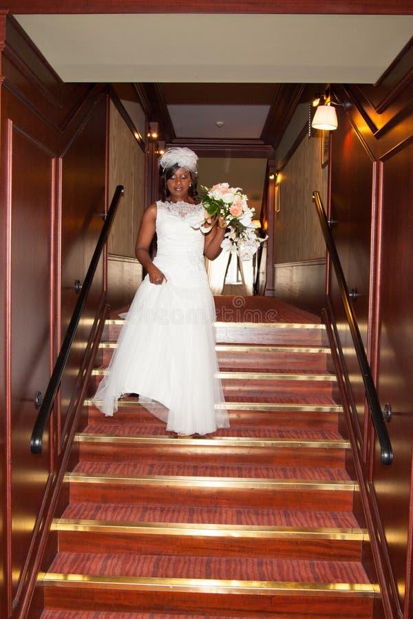 Det nätta afrikansk amerikanbrudinnehavet blommar på trappa inomhus arkivfoton