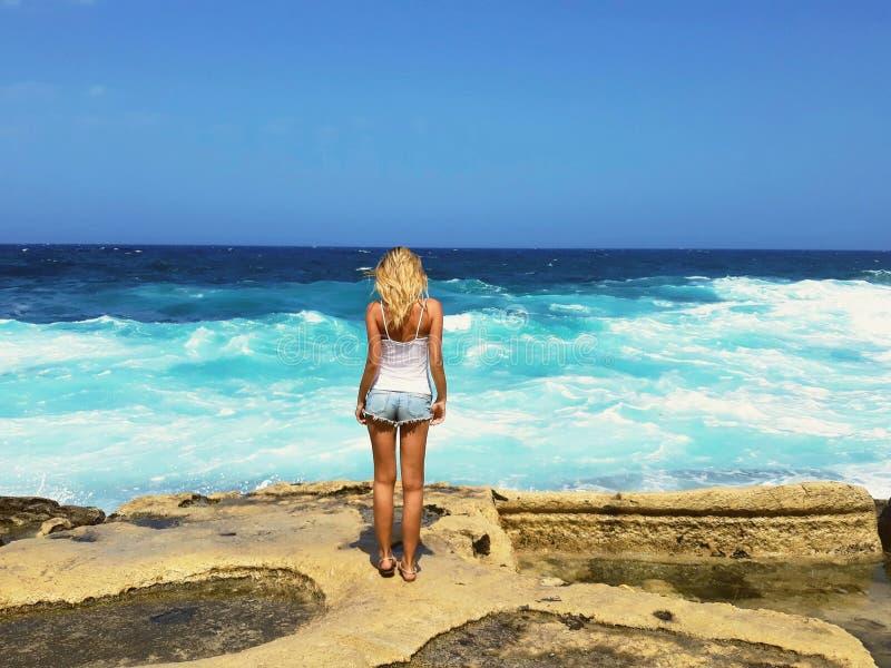 Det nätta anseendet för ung kvinna vaggar på att se ljusa havsvågor som är utomhus-, modemodell, tror i hopp, resande turist, kän royaltyfri foto