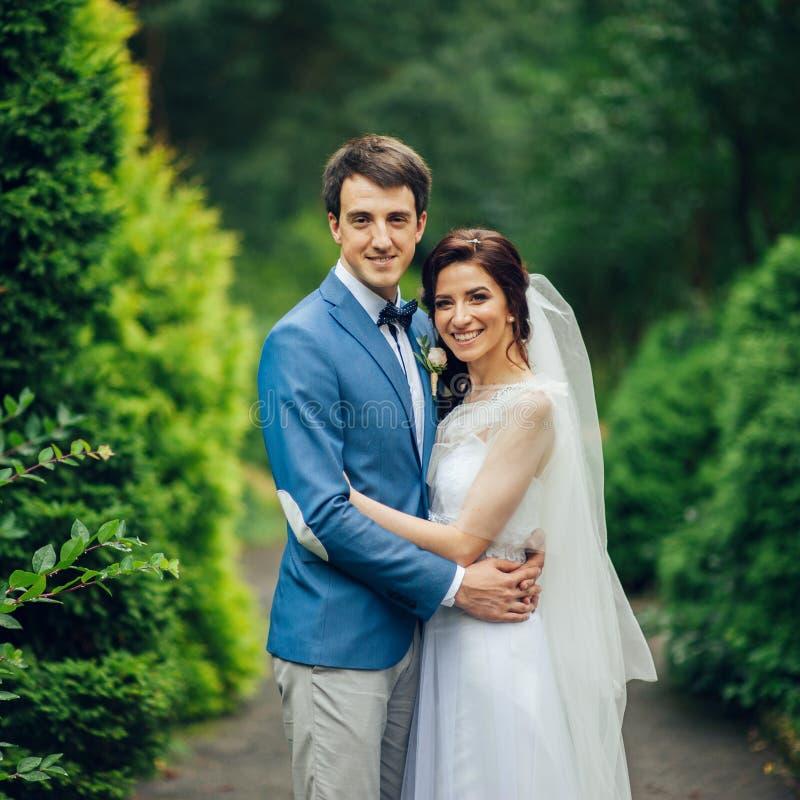 Det nätta bröllopparet poserar i en grön vårträdgård royaltyfri fotografi