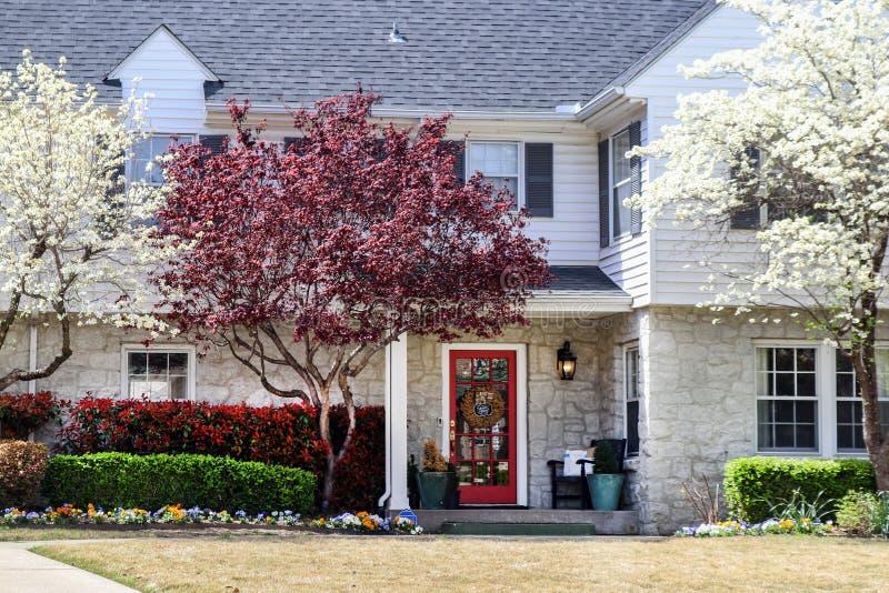 Det nätta huset för två berättelse med vaggar vit ramen för den botten och med slutare överst i vår med pansies och blomningträd  arkivbild