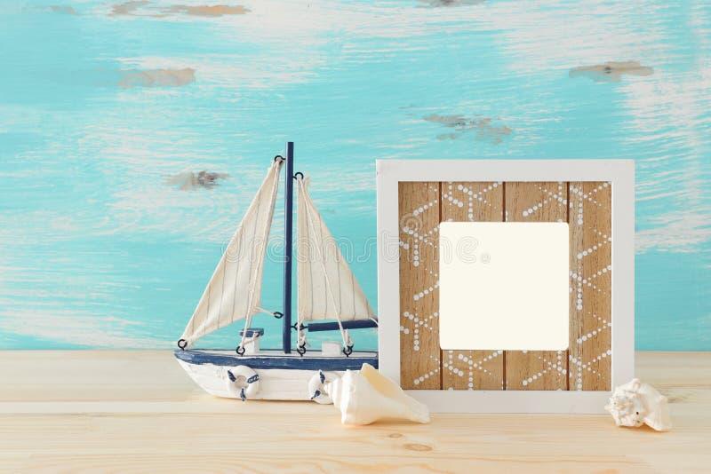Det nautiska begreppet med den tomma fotoramen och seglar fartyget ?ver tr?tabellen F?r fotografimontage fotografering för bildbyråer
