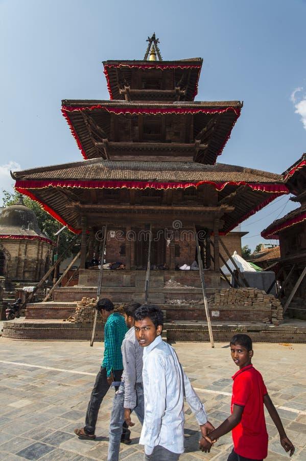 Det Nepali folket passerar en hinduisk tempel, som skadade vid jordskalv, Katmandu, Nepal royaltyfria bilder