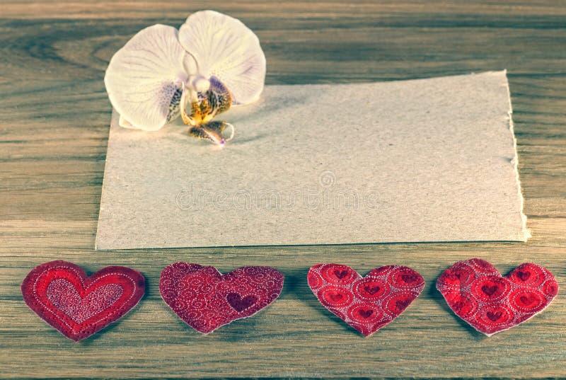 Det netto kortet för lyckönskan, hjärta och orkidén blommar på en lantlig träbakgrund royaltyfri foto