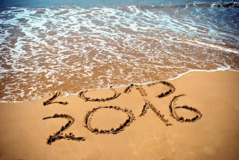 Det nya året 2016 är det kommande begreppet - inskriften 2015 och 2016 på en strandsand arkivfoto