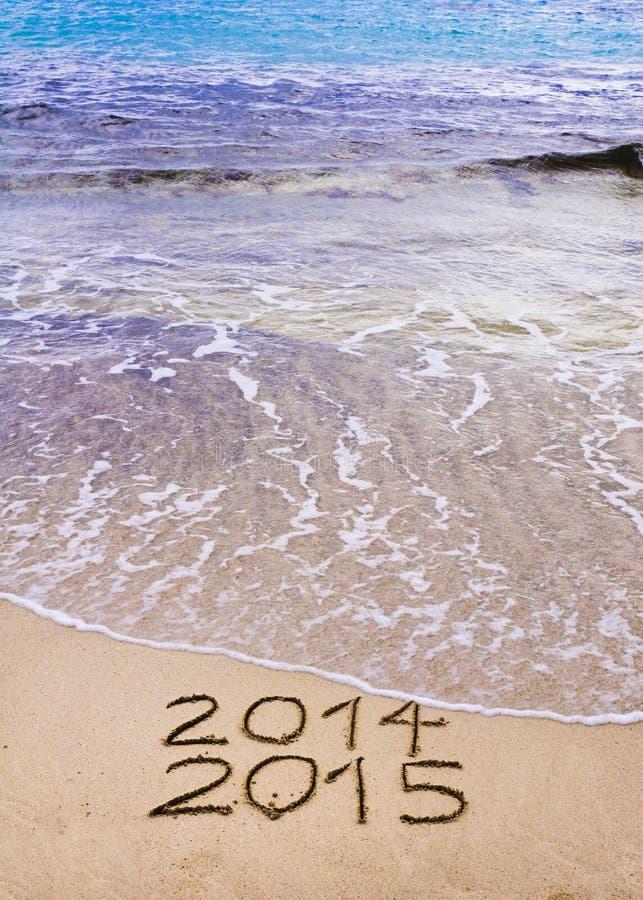 Det nya året 2015 är det kommande begreppet - inskriften 2014 och 2015 på en strandsand, vågen täcker 2014 royaltyfria foton