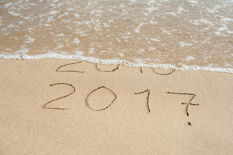 Det nya året 2017 är det kommande begreppet - inskriften 2016 och 2017 på en strandsand, vågen täcker nästan siffrorna 2016 royaltyfri foto
