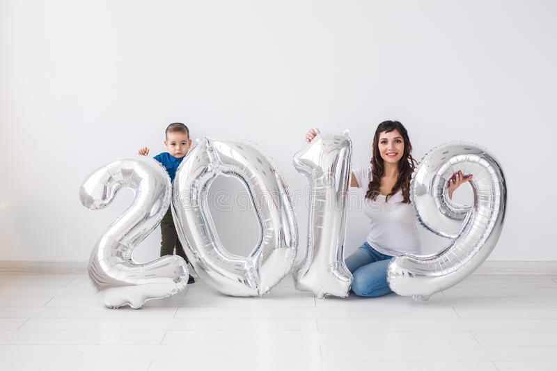 Det nya 2019 året är det kommande begreppet - den lyckliga modern och sonen med kulöra nummer för silver inomhus royaltyfria foton
