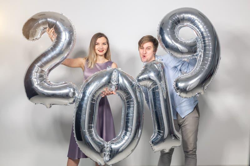 Det nya 2019 året är det kommande begreppet - den lyckliga unga mannen och kvinnan rymmer för att försilvra kulöra nummer på vit  royaltyfri foto